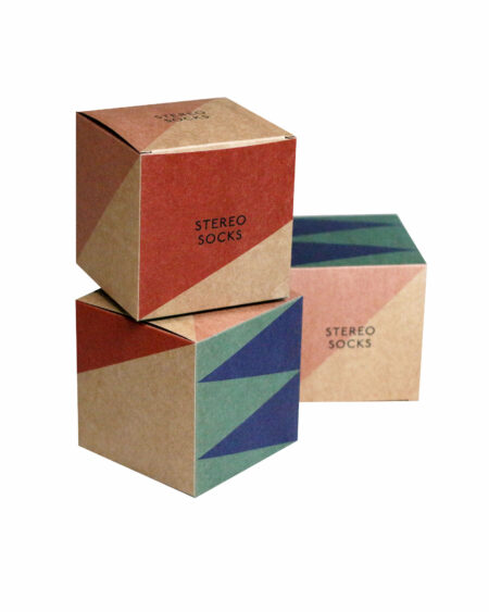 Drei Kartonwürfel mit farbigem geometrischem Muster und Stereo Socks Logo